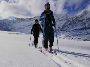 Due persone salgono sulla vetta della montagna con gli scia da alpinismo